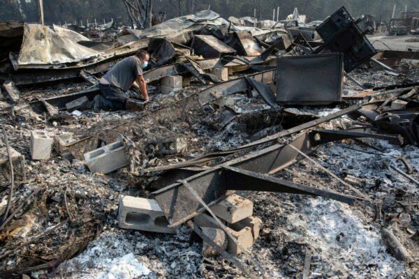 Jon Marshall looks through the debris of his home
