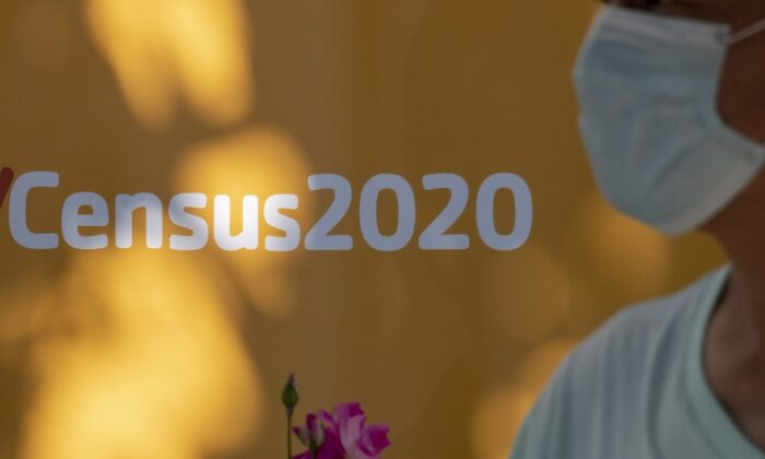 A man wearing a facemask walks past a sign encouraging people to complete the 2020 U.S. Census in Los Angeles, California, on Aug. 10, 2020. (Robyn Beck/AFP via Getty Images)