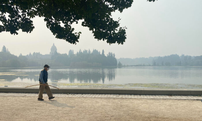 A man walks by the lake outside of the Washington State Capitol in Olympia, Wash., on Sept. 11, 2020. (Rachel La Corte/AP Photo)