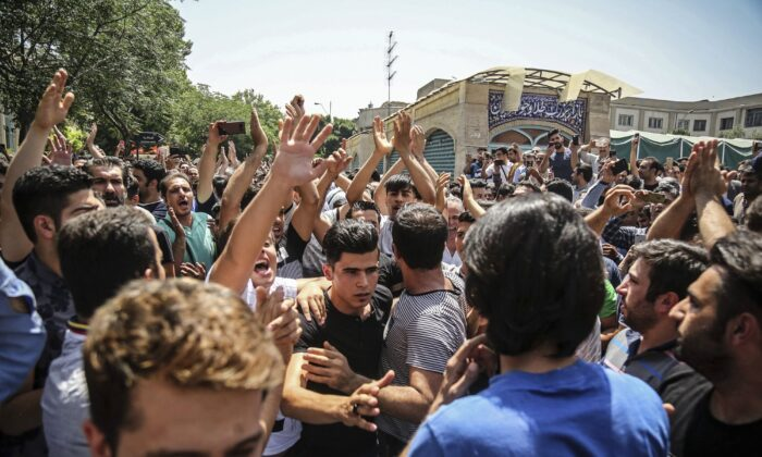 A group of protesters chant slogans at the main gate of the Old Grand Bazaar, in Tehran, Iran on June 25, 2018. (Iranian Labor News Agency via AP)