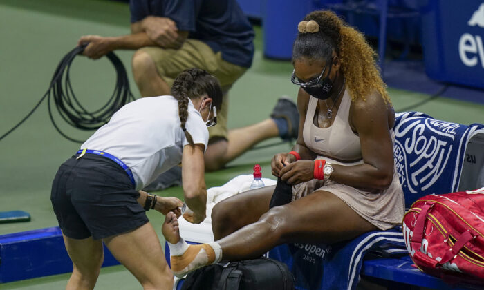Serena Williams, of the United States, has her ankle taped by a trainer during a medical timeout during a semifinal match of the U.S. Open tennis championships against Victoria Azarenka, of Belarus, Thursday, Sept. 10, 2020, in New York. (Seth Wenig/AP Photo)