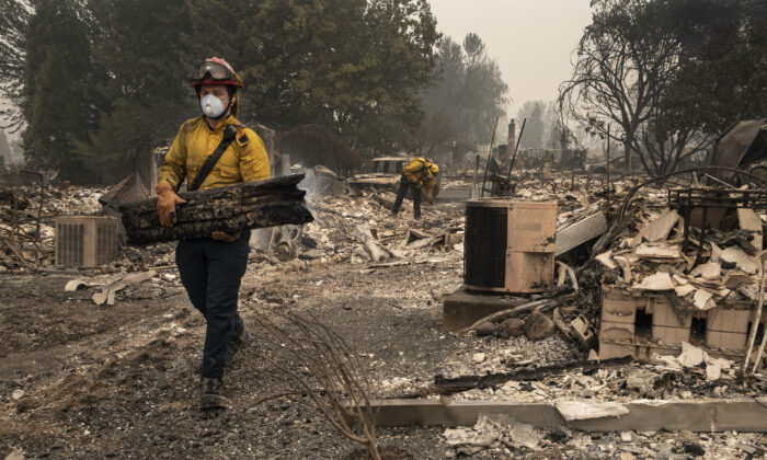 Jackson County District 5 firefighter Captain Aaron Bustard works on a smoldering fire in a burned neighborhood in Talent, Ore., Friday, Sept. 11, 2020, as destructive wildfires devastate the region. (Paula Bronstein/AP Photo)