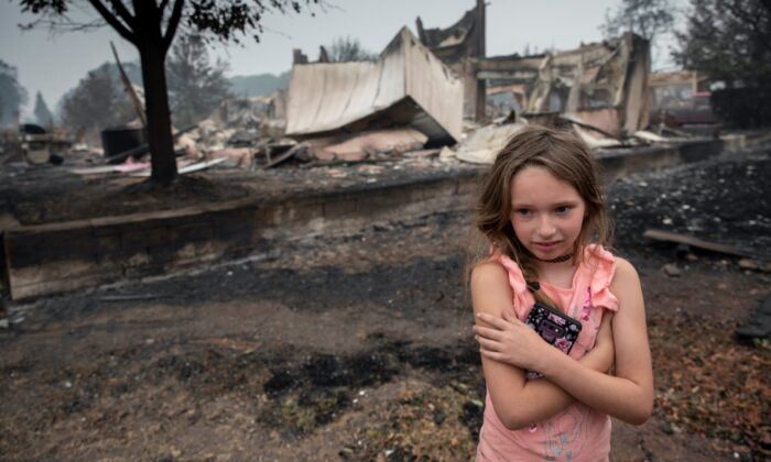 Ellie Owens, 8, from Grants Pass, Ore., looks at fire damage as destructive wildfires devastate the region in Talent, Ore., on Sept. 11, 2020. (Paula Bronstein/AP Photo)