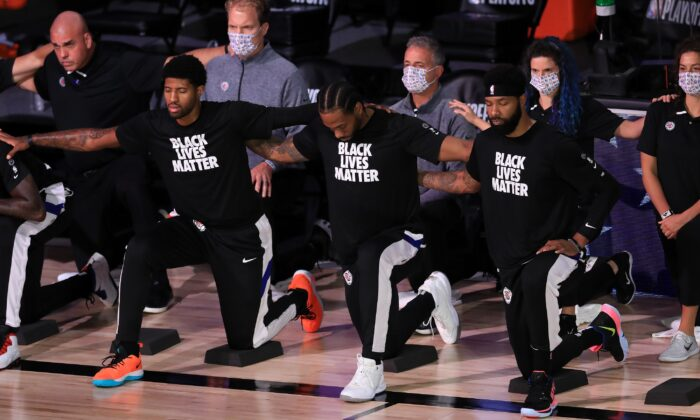 Los Angeles Clippers players and staff kneel during the national anthem before their game against the Denver Nuggets at the ESPN Wide World Of Sports Complex in Lake Buena Vista, Fla., on Sept. 11, 2020. (Michael Reaves/Getty Images)