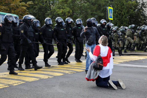 A protester knees in front of law enforcement officers Minsk
