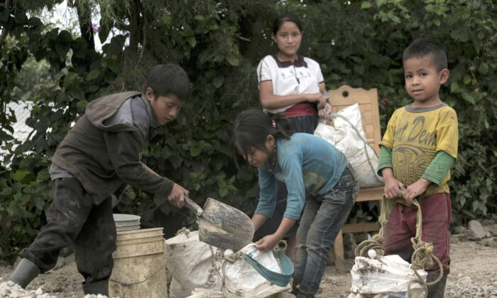 Children between the ages of 5 and 14 load gravel as they haul loads of construction materials to assist their families who have received government aid to build homes, in the Aldama district of Chiapas State, Mexico, Monday, Aug. 24, 2020. As students across Mexico restarted online and TV classes Monday amid the ongoing coronavirus pandemic, many children in remote rural areas without access to television or internet service were left out, with no way to restart their education. (AP Photo/Isabel Mateos)