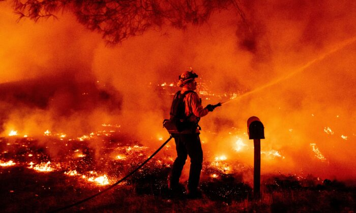 A Butte county firefighter douses flames at the Bear fire in Oroville, Calif., on Sept. 9, 2020. (Josh Edelson/AFP via Getty Images)