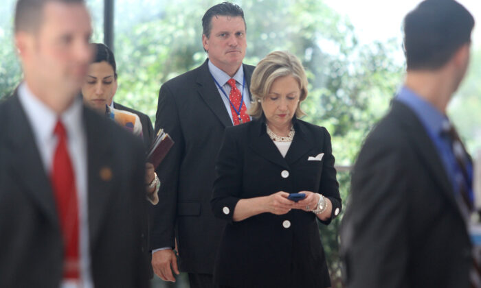Then-Secretary of State Hillary Clinton (C) looks at her mobile phone in Hanoi, Vietnam, on July 23, 2010. (Na Son Nguyen/AFP via Getty Images)