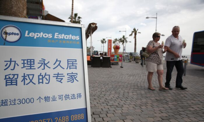 Tourists walk past a real estate promotion billboard—with text in Chinese that states buying an apartment can earn permanent resident status—on the seafront promenade in the Cypriot resort of Paphos on Jan. 24, 2013.(Yiannis Kourtoglou/AFP via Getty Images)