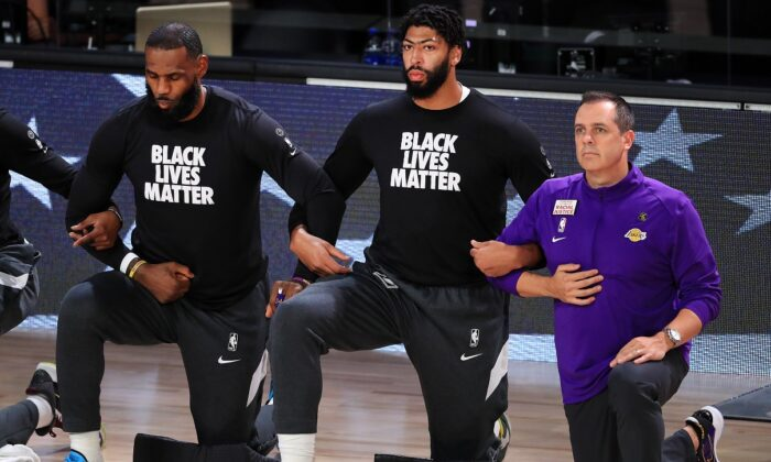 LeBron James (L) of the Los Angeles Lakers, Anthony Davis (C) of the Los Angeles Lakers, and Frank Vogel (R) of the Los Angeles Lakers kneel during the National Anthem prior to the start of the game against the Houston Rockets in Game Five of the Western Conference Second Round during the 2020 NBA Playoffs in Lake Buena Vista, Fla., on Sept. 12, 2020. (Michael Reaves/Getty Images)