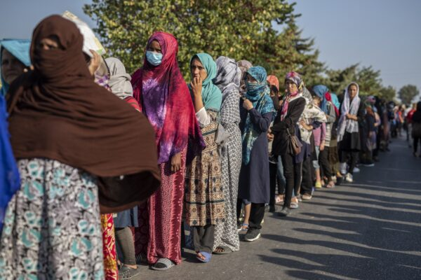 Migrants wait in a queue for food distribution