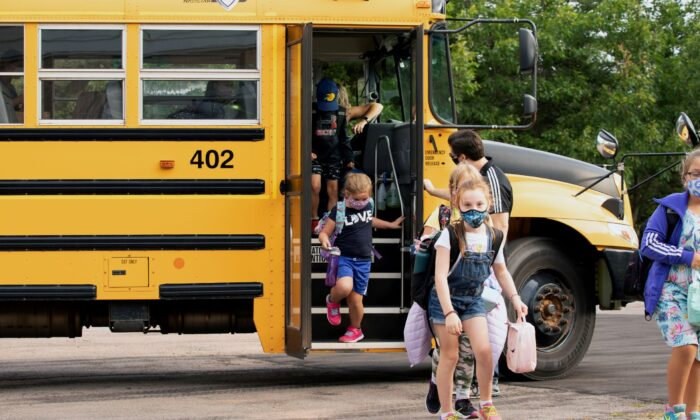Children get off the school bus as schools reopen with measures in place to prevent the spread of the CCP virus in Vernon Bridge, Prince Edward Island, Canada, on Sept. 8, 2020. (John Morris/Reuters)