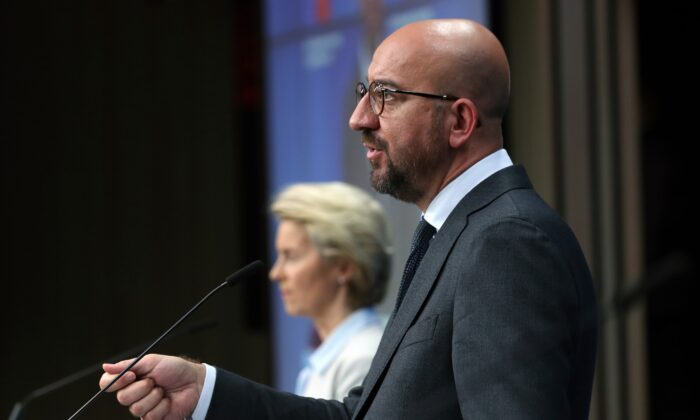 European Council President Charles Michel talks during an online press conference with European Commission President Ursula von der Leyen, background, and German Chancellor Angela Merkel following an EU-China virtual summit at the European Council building in Brussels, Belgium, on Sept. 14, 2020. (Yves Herman/Pool Photo via AP)