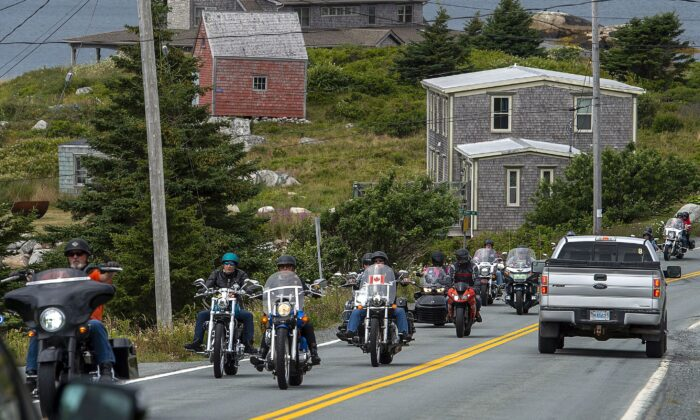 Motorcyclists leading a ceremonial drive to honour the victims of April's mass killings pass through Indian Harbour, N.S., on Aug. 15, 2020. The event was organized by Harry Bond, who lost his parents in the murder rampage that claimed 22 lives. (The Canadian Press/Andrew Vaughan)