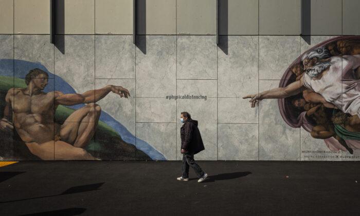 A man wearing a mask walks past street art in South Melbourne, Australia on September 14, 2020 in Melbourne.(Daniel Pockett/Getty Images)
