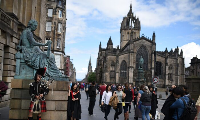 A street performer plays the bagpipes next to a statue of Scottish philosopher David Hume on the Royal Mile in Edinburgh, Scotland, on June 25, 2016. (Oli Scarff/AFP via Getty Images)