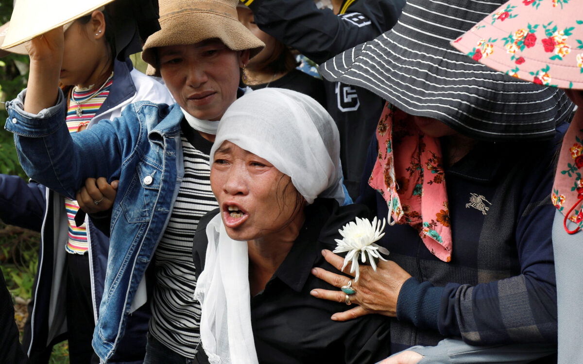 Tran Thi Hien cries while following an ambulance carrying her daughter's coffin during the funeral ceremony at her village in Nghe An province