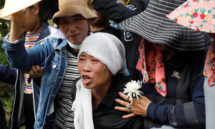 Tran Thi Hien, mother of Anna Bui Thi Nhung, one of 39 Vietnamese people found dead in a truck in England in October 2019, cries while following an ambulance carrying her daughter's coffin during the funeral ceremony at her village in Nghe An province, Vietnam, on Nov. 30, 2019. (Kham/Reuters)
