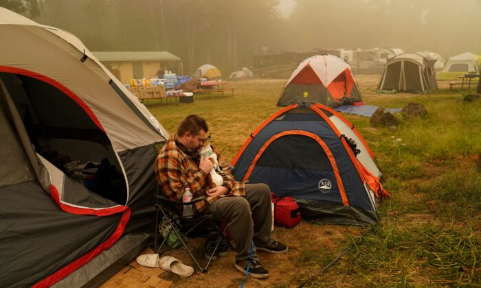 Kristopher Smith holds his dog Tripp outside his tent at an evacuation center at the Milwaukie-Portland Elks Lodge, in Oak Grove, Ore., on Sept. 13, 2020. (John Locher/AP Photo)