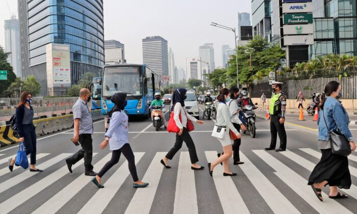People wearing masks as a precaution against the new coronavirus outbreak, walk on a pedestrian crossing at the main business district in Jakarta, Indonesia, on Sept. 14, 2020. (Tatan Syuflana/AP Photo)