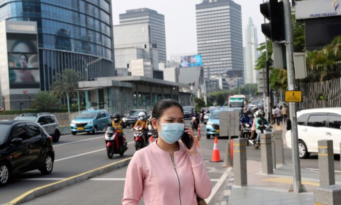 A woman, wearing a face mask as a precaution against the COVID-19, talks on her mobile phone on the sidewalk of a street at the main business district in Jakarta, Indonesia, on Sept. 14, 2020. (Tatan Syuflana/AP Photo)