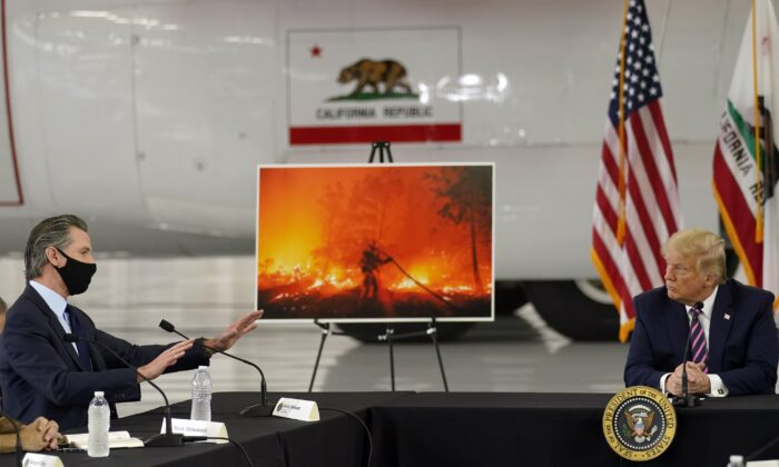 President Donald Trump listens as California Gov. Gavin Newsom speaks during a briefing at Sacramento McClellan Airport in McClellan Park, Calif., on Sept. 14, 2020. (Andrew Harnik/AP Photo)