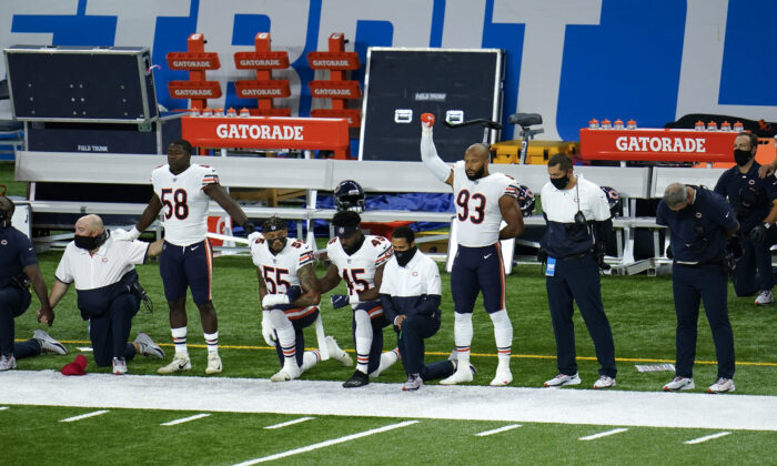 Chicago Bears Roquan Smith (58), Josh Woods (55), Joel Iyiegbuniwe (45) and James Vaughters (93) kneel during the national anthem before an NFL football game against the Detroit Lions in Detroit, Mich., Sept. 13, 2020. (Paul Sancya/AP Photo)