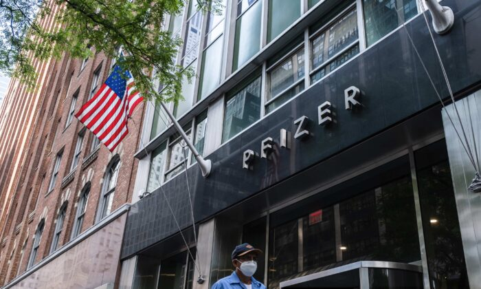 A pedestrian wearing a protective mask walks past the Pfizer headquarters in New York City on July 22, 2020. (Jeenah Moon/Getty Images)
