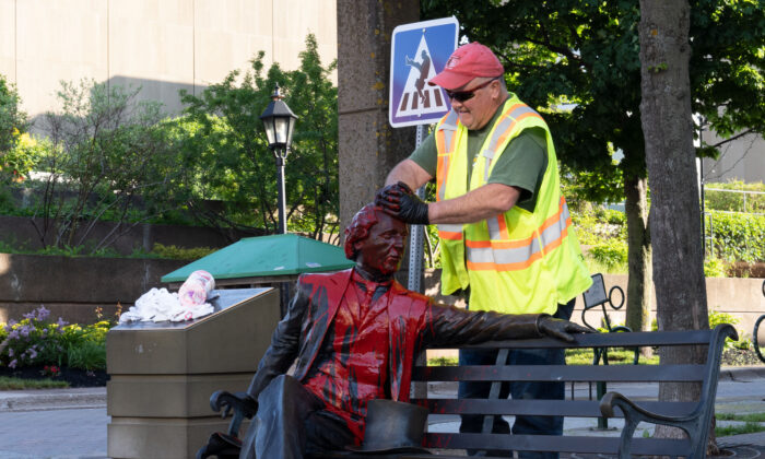 Ivan Mcguigan, of the Charlottetown Public Works department, cleans Sir John A Macdonald statue in Charlottetown after red paint was dumped on the statue on Friday June 19, 2020.The canadian Press/John Morris