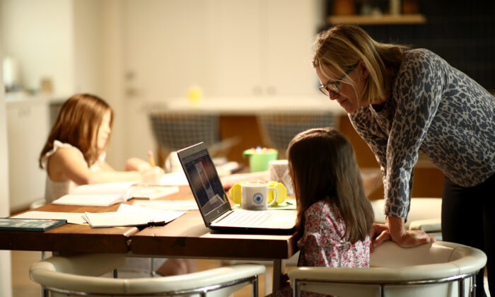 Daisley Kramer helps her kindergarten daughter, Meg, with schoolwork at home in San Anselmo, Calif., on March 18, 2020. (Ezra Shaw/Getty Images)