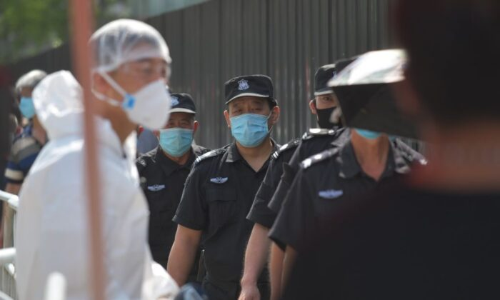 Security guards wait in line to undergo COVID-19 coronavirus swab tests at a testing station in Beijing on June 30, 2020. (Greg Baker/AFP via Getty Images)