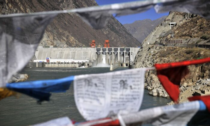 This picture taken on Nov. 23, 2014, shows prayer flags hanging before the Zangmu Hydropower Station in Gyaca county in Lhoka, or Shannan prefecture, southwest China's Tibet region. (