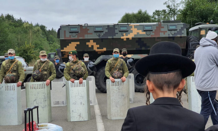 Jewish pilgrims, who plan to enter Ukraine from the territory of Belarus, gather in front of Ukrainian service members near Novi Yarylovychi crossing point in Chernihiv Region, Ukraine, on Sept. 15, 2020. (Breslev live/Handout via Reuters)