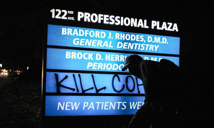 """A masked individual spray paints the words """"Kill Cops"""" on a business sign during protests in Portland, Ore., on Sept. 5, 2020. (Allison Dinner/AFP/Getty Images)"""