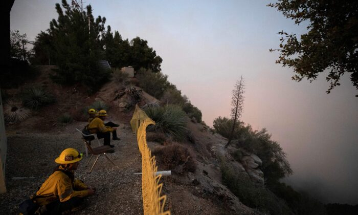 Firefighters watch as smoke rises near Mount Wilson Observatory from the Bobcat Fire in Los Angeles, Calif., on Sept. 14, 2020. (Mario Anzuoni/Reuters)