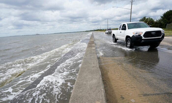 Waters from the Gulf of Mexico pour onto a local road, in Waveland, Miss., on Sept. 14, 2020. (Gerald Herbrt/AP Photo)