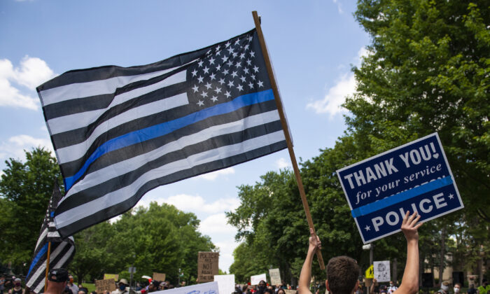 """A demonstrator holds a """"Thin Blue Line"""" flag at a protest on June 27, 2020 in St Paul, Minnesota. (Stephen Maturen/Getty Images)"""