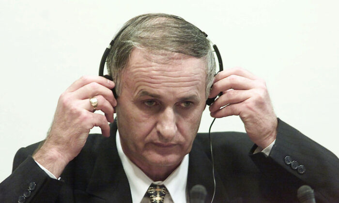 Bosnian Serb Gen. Radislav Krstic puts on headphones as he takes his seat in the courtroom in The Hague, Netherlands, on Aug. 2, 2001. (Ed Oudenaarden/Pool Photo via AP, File)