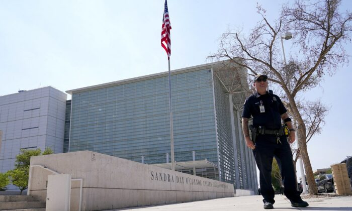 A Phoenix Police officer stands in front of the Sandra Day O'Connor U.S. Courthouse in Phoenix, on Tuesday, Sept. 15, 2020. A drive-by shooting wounded a federal court security officer Tuesday outside the courthouse in downtown Phoenix, authorities said. The officer was taken to a hospital and is expected to recover, according to city police and the FBI, which is investigating. (AP Photo/Ross D. Franklin)