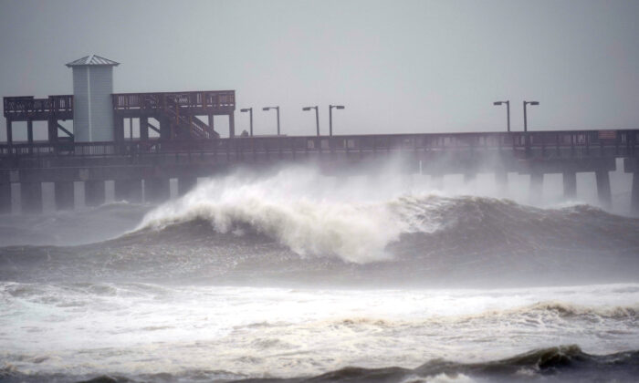 Waves crash near a pier, at Gulf State Park, in Gulf Shores, Ala. on Sept. 15, 2020. (AP Photo/Gerald Herbrt)