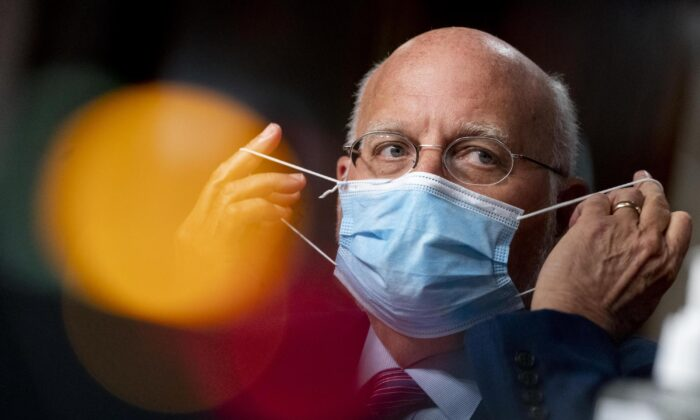 Centers for Disease Control and Prevention (CDC) Director Dr. Robert Redfield puts his mask on after speaking at a hearing of the Senate Appropriations subcommittee reviewing CCP virus response efforts in Washington, on Sept. 16, 2020. (Andrew Harnik-Pool/Getty Images)