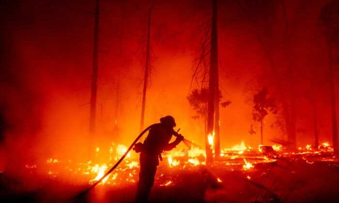 A firefighter battles the Creek Fire as it threatens homes in the Cascadel Woods neighborhood of Madera County, Calif., on Sept. 7, 2020. (Noah Berger/AP Photo)