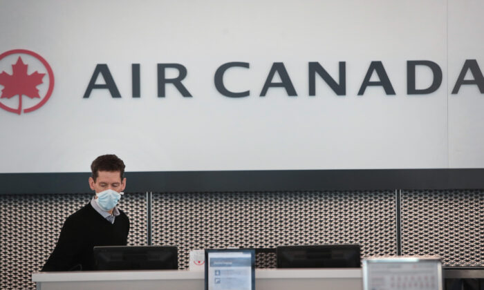 An Air Canada worker waits for travellers at a nearly-empty O'Hare International Airport in Chicago, Ill,. on April 2, 2020. (Scott Olson/Getty Images)