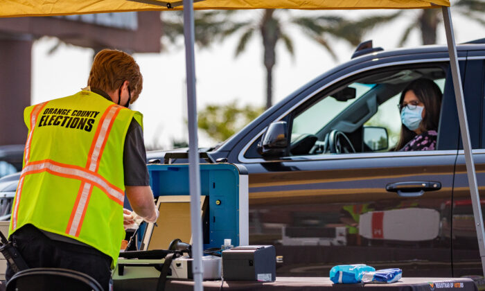 An Orange County election worker demonstrates the drive-thru voting process outside the Honda Center in Anaheim, Calif., on Sept. 16, 2020. (John Fredricks/The Epoch Times)