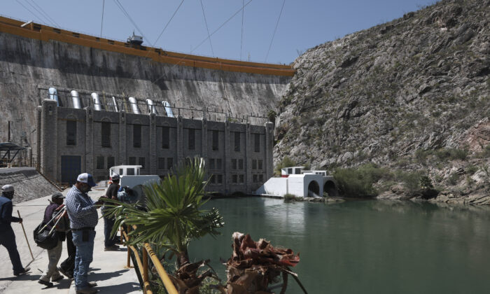 Farmers stand at La Boquilla Dam, where they wrested control from National Guard troops in order to close the valves and reduce the flow of water toward the United States, in Chihuahua State, Mexico, on Sept. 9, 2020. (Christian Chavez/AP Photo)