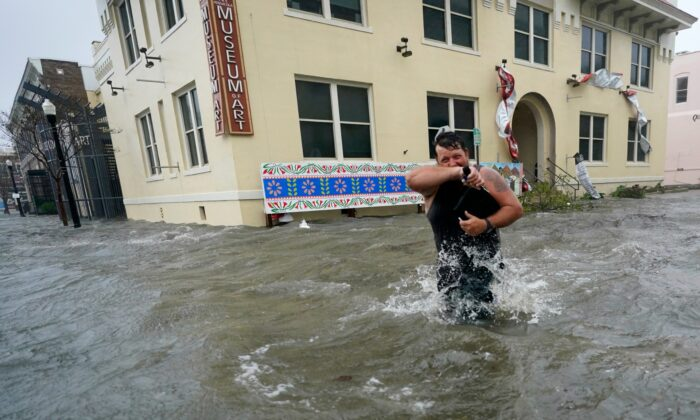 Trent Airhart wades through floodwaters, in downtown Pensacola, Fla., on Sept. 16, 2020. (Gerald Herbert/AP Photo)