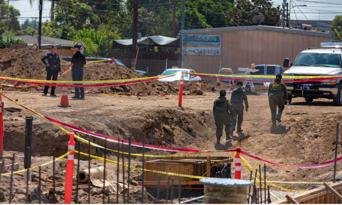 Detectives from the Santa Ana Police Department and the Orange County Sheriff's Department Coroner Division investigate the construction site where human bones were discovered in Santa Ana, Calif., on Sept. 17, 2020. (John Fredricks/The Epoch Times)
