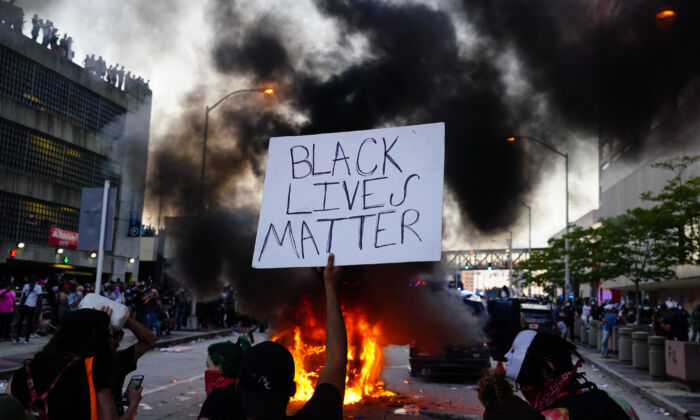 A man holds a Black Lives Matter sign as a police car burns in front of him during a protest outside CNN Center in Atlanta, Georgia on May 29, 2020. (Elijah Nouvelage/Getty Images)