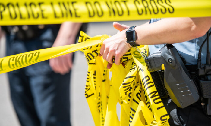 A police officer rolls up caution tape in a file photo. (Brandon Bell/Getty Images)