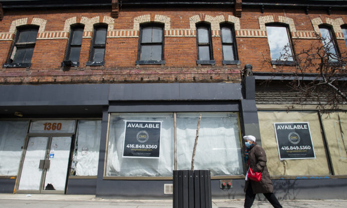 A pedestrian walks past a closed business on Queen Street in Toronto on April 16, 2020. (Nathan Denette/The Canadian Press)